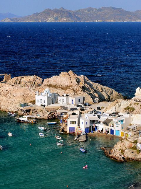 """Fyropotamos (Milos island). The picturesque village of Fyropotamos is both a fishing port and a beach with amazing blue water. It is very small, with a couple of houses with """"syrmata"""". Syrmata are called in Milos the places of storage of small vessels on the ground floor of the houses, just in front of the sea. The vivid colors, with which are their exterior painted, give a special look to the traditional landscape of the island   Sporades, Greece."""