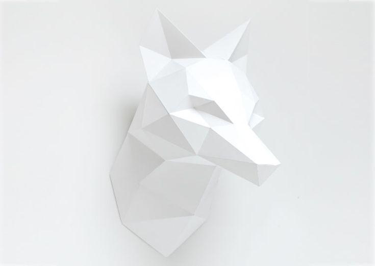 Une tête de renard blanche sous forme de kit pour créer un grand trophée mural de papier. Ce kit contient 3 grandes feuilles de papier, une règle de pliage, un tube de colle et les explications d'assemblage pour réaliser soi-même son trophée renard.