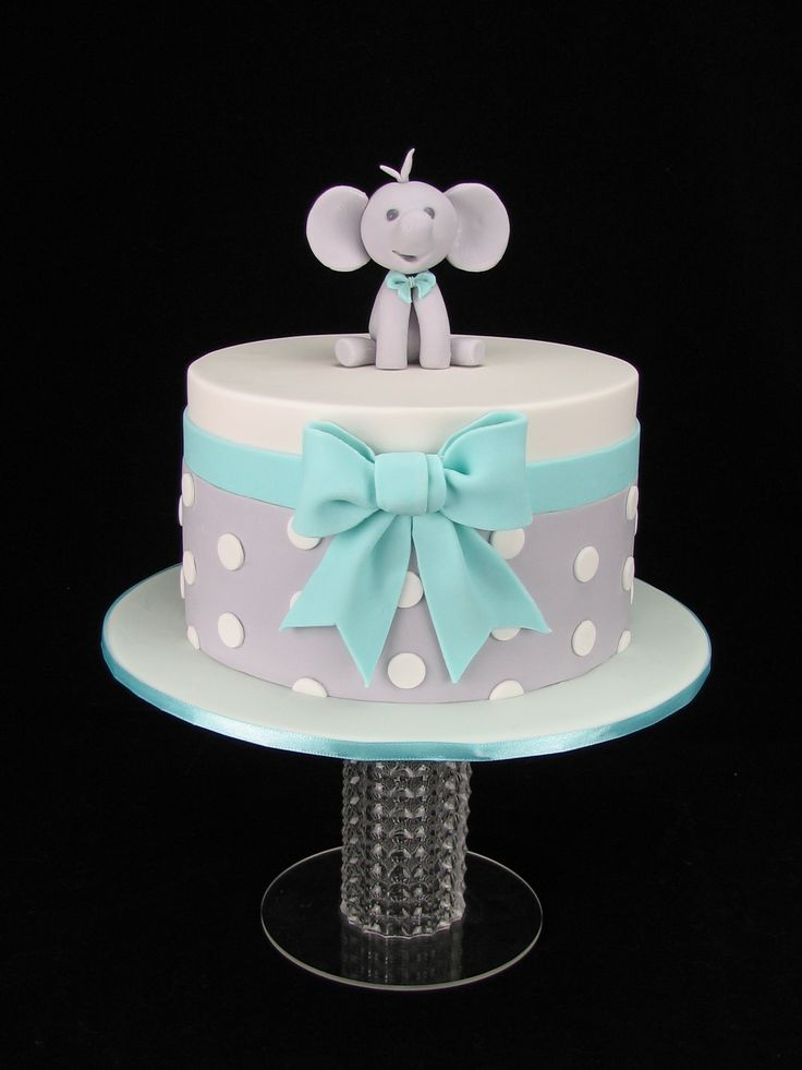 A cute baby shower cake in chocolate mud with chocolate ganache and covered in fondant. The little elephant and bow are hand made from fondant.