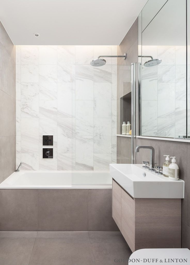 Detail of the family bathroom featuring Vola marble tiles on the back wall and large format beige porcelain tiles on the other walls and floor. Hansgrohe brassware. Catalano santiary ware and our bespoke bathroom cabinet. GD&LBespokeFurniture