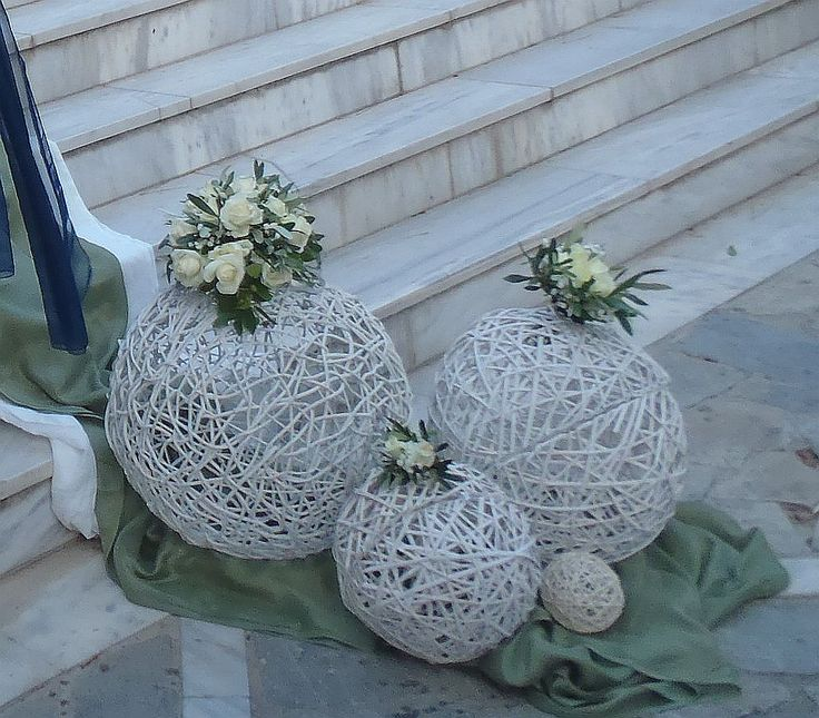 Στολισμός στα σκαλιά της εκκλησίας με μπάλες μπαμπού. Πάνω σε λαδί και λευκά υφάσματα τοποθετήσαμε λευκές μπάλες μπαμπού τις οποίες διακοσμήσαμε με ελιά και συνθέσεις από τριαντάφυλλα λευκά.