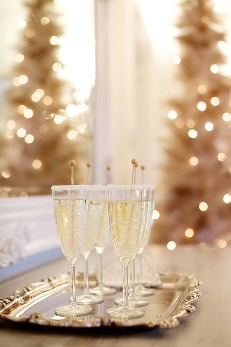 Shimmering Christmas cocktails on a sterling silver tray, with a gold Christmas tree in the background -- perfect holiday party decor idea!