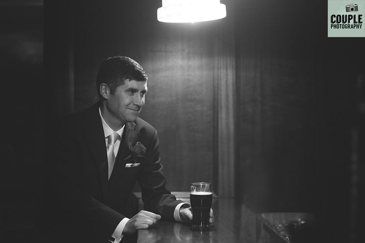 The groom channels old black and white films as he has a pint at the bar. Weddings at The Westgrove Hotel by Couple Photography.
