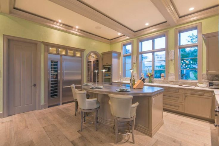 Kitchen: Airy Transitional Kitchen With Yellow Green Walls And Eat In Island With Individual Spot Lights Also Stainless Steel Refrigerator. large refrigerator. wine refrigerator. stainless steel refrigerator. pale kitchen. curved kitchen island. leather barstools. wood flooring.