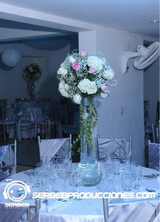 Centro de mesa floral manejando rosas, hortensias y follaje.