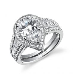 This unique 18K white gold diamond engagement ring features a 2.75 carat pear cut center diamond. Accentuated by surrounding round diamonds and baguette diamonds down the shank, designed to enhance the center diamond, contains a total 1.16 carats. The diamond engagement ring is available in any shape or size center diamond, in 18K white gold or platinum, with a flush fit wedding band to match. (For pricing on this diamond engagement ring and other diamond engagement rings, contact a retailer…