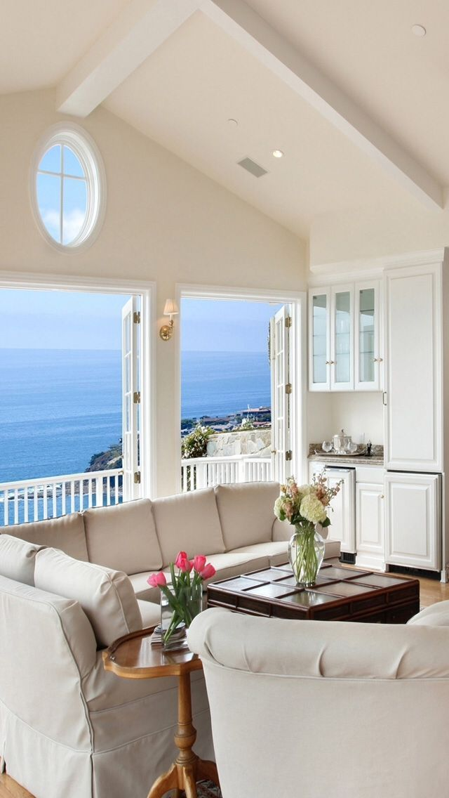Beach house sitting room with a balcony and an ocean view...beautiful windows...