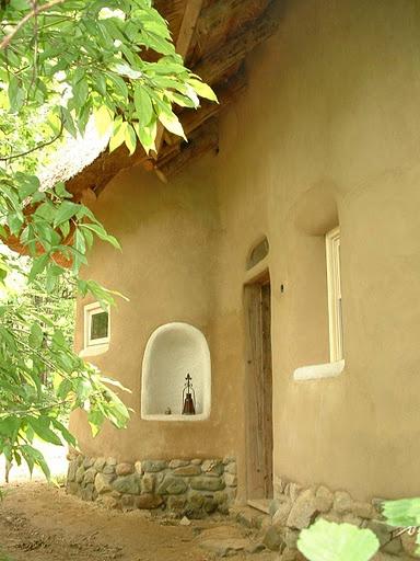Leem stucwerk bij een strobouw huis. Met een goed dakoverstek om de gevel te beschermen. Let ook op de plint van stenen.