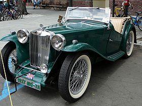 La MG TA Enano reemplazó el PB en 1936. [1] Fue una evolución del anterior coche y fue de 3 pulgadas (76 mm) más ancha en su pista a 45 pulgadas (1.100 mm) y 7 pulgadas (180 mm) más largo en su la distancia entre ejes en 94 pulgadas (2.400 mm).  El avanzado anterior árbol de levas motor cuatro en línea ahora no estaba en uso por ningún otro coche de producción por lo que fue sustituido por el MPJG OHV unidad de la Wolseley 10 pero con gemelos SU carburadores, árbol de levas modificado y la…