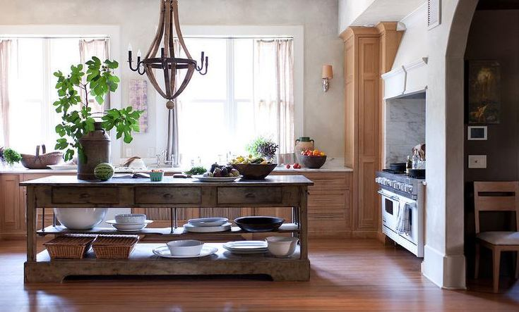 European style kitchen features a wood barrel chandelier illuminating a freestanding rustic center island with drawers and…