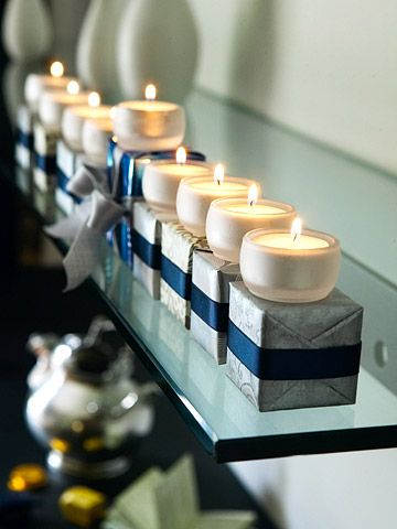 Individual tealight holders on silver and blue wrapped boxes, secured with double-stick tape.