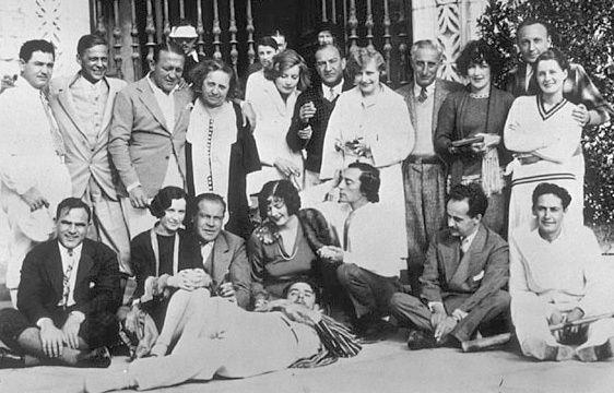 Back row, left to right, partially obscured: King Vidor, Beatrice Lillie, Richard Barthelmess, Eleanor Boardman.    Middle row: Frank Orsatti, E. B. Hatrick, Edmund Goulding, Mrs. Talmadge, Garbo, Nicholas Schenck, unidentified, Harry Rapf, Aileen Pringle, J. Robert Rubin, Norma Shearer.    Front row: Hal Roach, Natalie Talmadge, Eddie Mannix, Constance Talmadge, Buster Keaton, Paul Bern, Irving Thalberg.   John Gilbert reclines in foreground.   (William Randolph Hearst's castle, San…