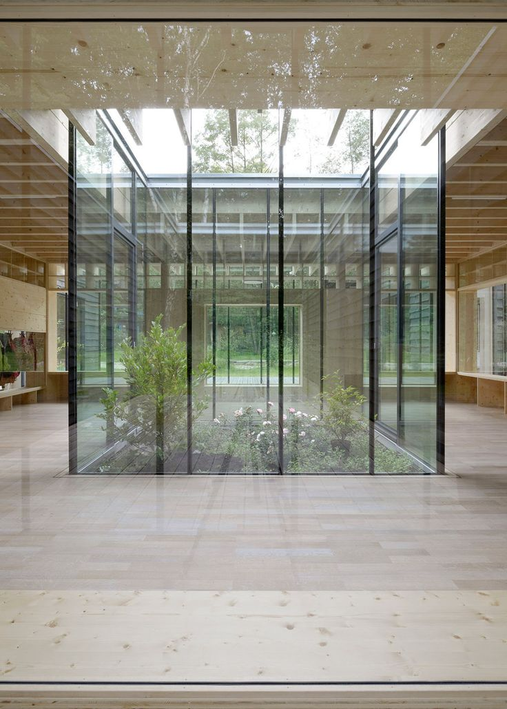 Roughly cut wooden planks clad classrooms arranged around a central glazed atrium at this nursery