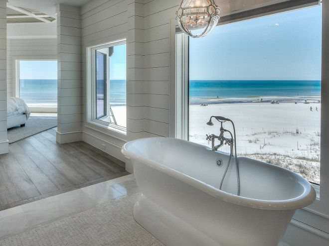Shiplap walls, marble floors and freestanding tub. Oh, and let's hope that is a private beach... yes, please!!