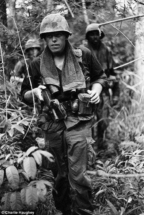 Tough: Soldiers wore towels around their necks to wipe away sweat in the relentless jungle heat in Vietnam
