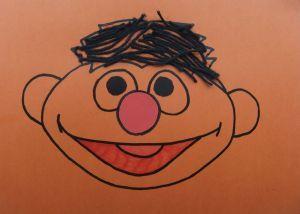 Een zelfgemaakte Ernie-uitnodiging. Laat je kind er de haartjes van zwarte wol opplakken.