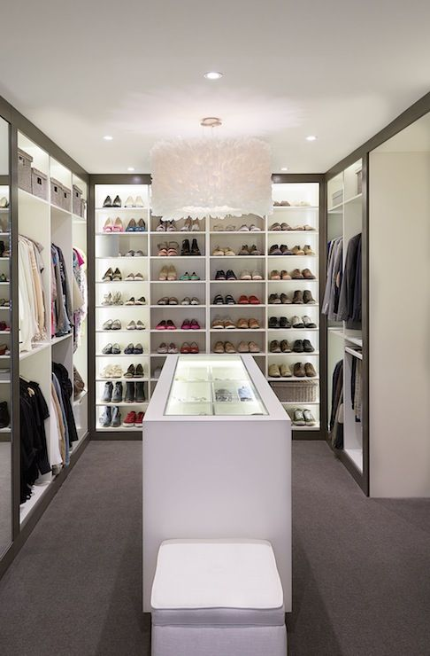 Amazing closet featuring white goose quill feather chandelier over white lacquered closet island with glass display top. Walk-in closet features floor to ceiling built-in cabinets, built-in mirror and shelves for shoes. -- Luxury home interior design, decor, and decorating ideas --