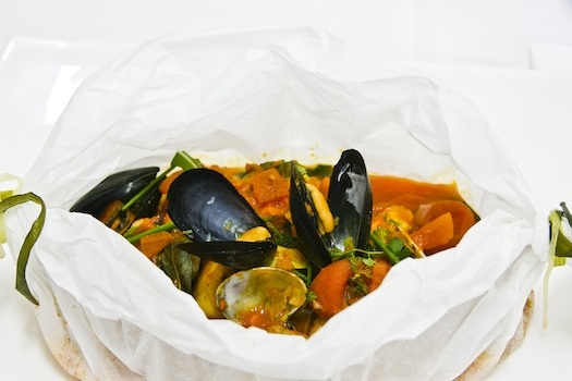 Zuppa di pesce in cartoccio con verdure dell'orto Un classico che apre i suoi profumi a tavola