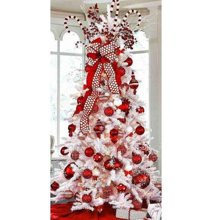 Extravagante, esta árvore se inspirou no candy cane, o doce listrado branco e vermelho em forma de bengala que decora o topo, e optou por ramos totalmente brancos e ornamentos nas duas cores.