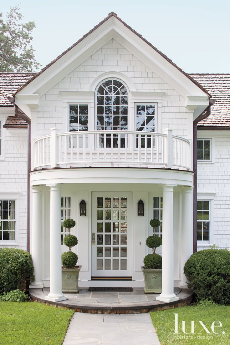 A new portico enhances the sense of entry, which is also boosted by topiaries planted in vintage pots through M. Frederick.