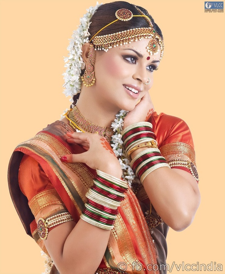 The Andhra Bridal look brings out the best in the bride with deep kohl lined eyes, thickened lashes and a sprinkle of shimmer on the eyelids. The lips are kept light with gloss, while the hair is swept up either in a French roll or an elegant upstyle that matches the overall look. A more traditional, long plait adorned with fresh flowers is also an option.