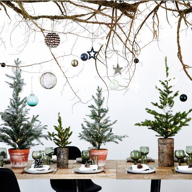 Optez pour des petits sapins de Noël en guise de centre de table. Installés dans des pots en terre cuite, pour une décoration bohème, ils s'agrémentent sobrement de petits objets et apporte une touche ultra originale.