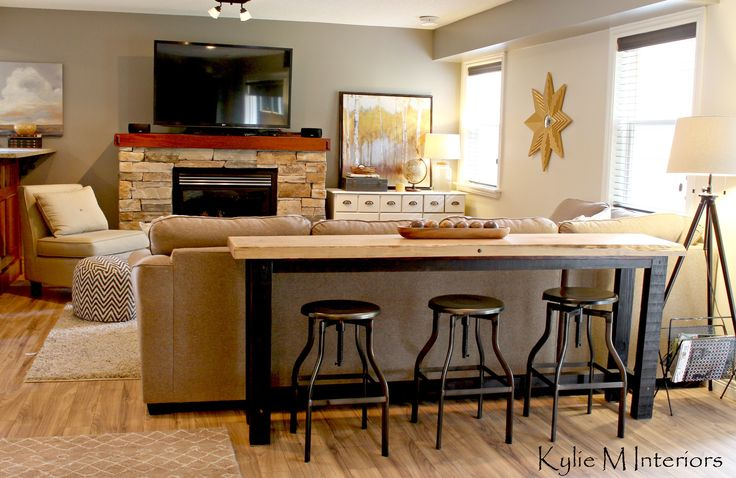 man or guy friendly family room decorating ideas with a bar table and stools behind the sectional to watch tv with sherwin williiams pewter tankard and live edge wood table behind sectional couch