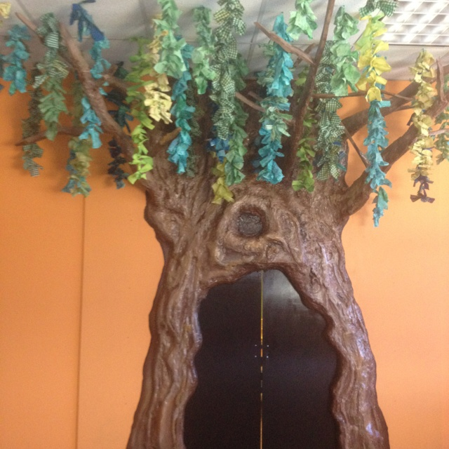 3-D tree built out of wood, insulation spray foam, and plaster. Leaves are made by strips of dyed material tied together.