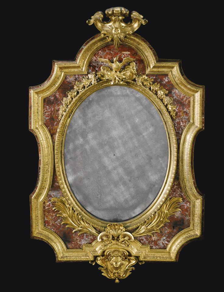 A Italian gilt-bronze and Sicilian jasper mounted frame, Roman or Neapolitan first half 18th century the arched cresting with a sunburst motif above a later oval mirror plate within a lunette cast border surmounted by an eagle amongst clouds with foliate trails, with a jasper ground within an engraved leaf cast border, the apron cast with a stylised scallopshell flanked by c-scrolls and sprays of palm leaves above a female mask with plaits terminating in a tassel and scallopshell with a…