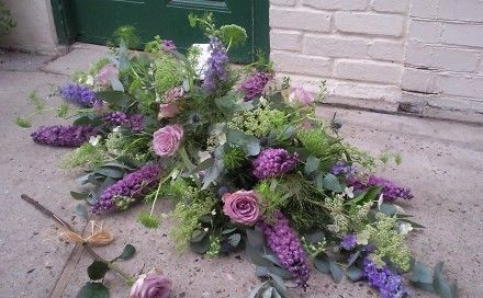 lilac and mauve casket spray with garden-style roses and delphiniums