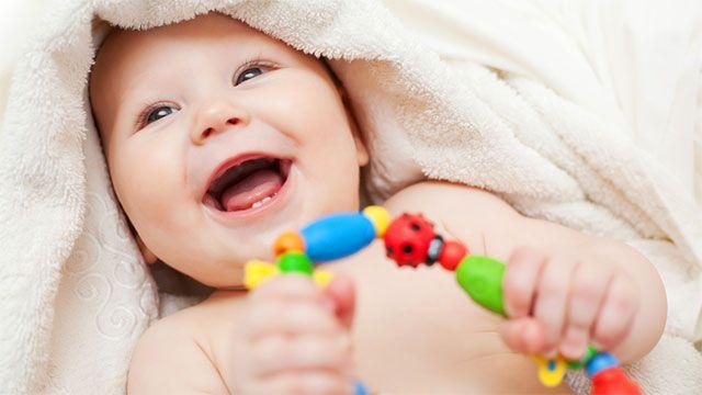 Süßes lachendes Baby mit Spielzeug / Greifring.