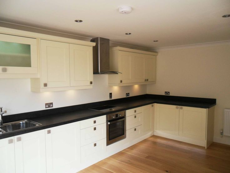 Magnificent Black Granite Countertop With Built In Stove With Wall Mount Euro Range Hood Stainless Steel Polished Plus L-shaped Cream Cabinets For Modern White Kitchen Ideas