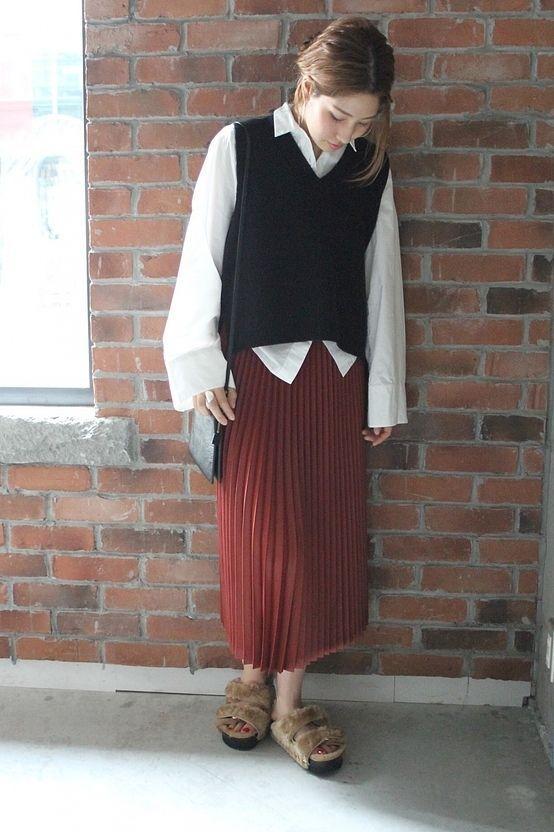スーパーファインメリノニットベスト  柔らかな風合のいいニットベストをシャツに重ねたスタイル。 ベーシックなコーディネートをボルドーのプリーツスカートで女性らしいスタイルに。 ファーのサンダルでキャッチーな印象をプラスしました。