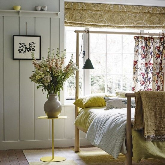 Country inspired bedroom with yellow fabrics and bed