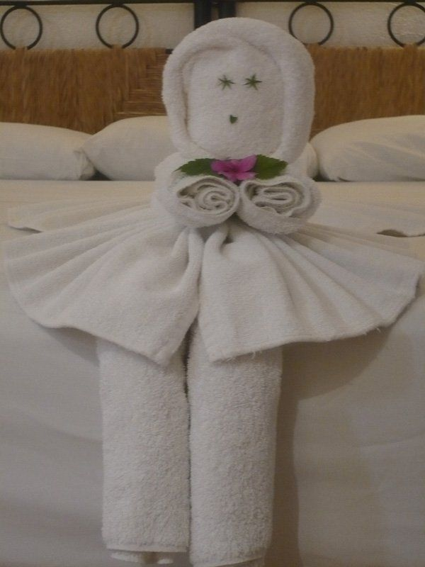 A cute baby doll towel origami. The doll like design is made to look like she is wearing a hood and dress and is carrying pink flowers.