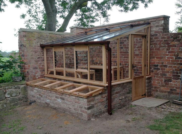 handcrafted timber greenhouse against garden brick wall