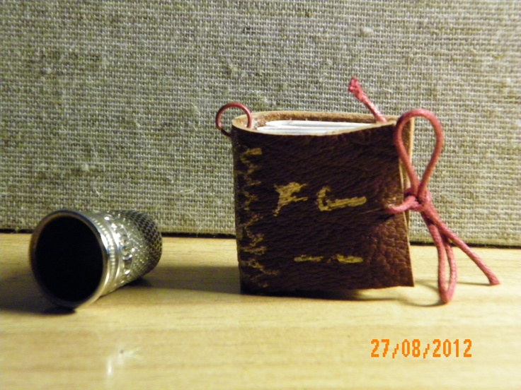 Leather hand-stitched mini book pendants. The color and design of the covers can easily be customized!