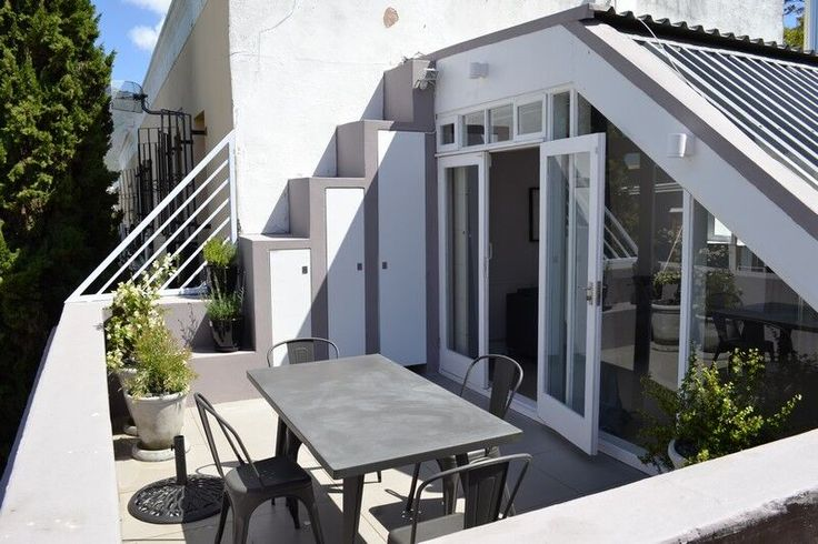 Stylishly furnished this contemporary property is situated on 55 Loader Street.  You enter into the bright white open plan ground floor kitchen and dining room with free-standing wood burning stove and exposed brick wall plus upright piano. | Holiday Houses SA