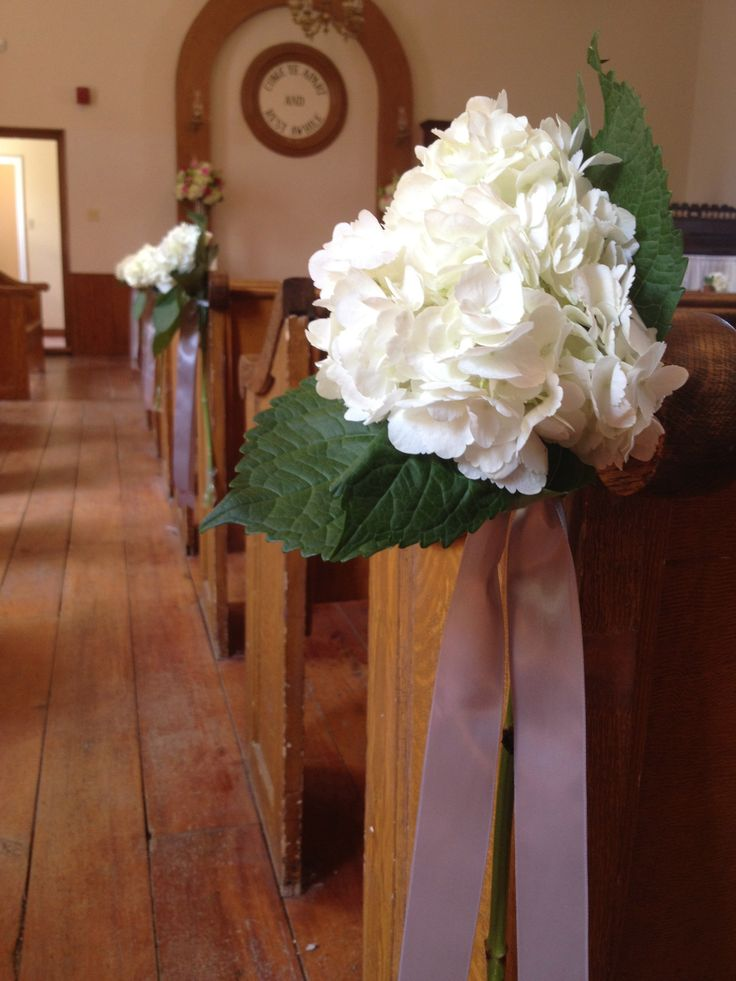 Stems of whit hydrangea were tied to the pews with grey satin ribbon