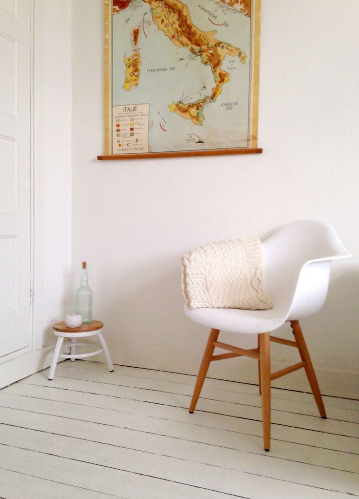 Detail van mijn kamer, met eames stoel, gebreide deken, landkaart, krukje en een witte, planken vloer.