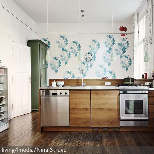 Die Kombination aus Edelstahl-Oberflächen und dunkler Holzverkleidung lassen diese Küchenzeile elegant und modern wirken. …