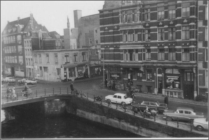 1964. De Jodenbreestraat is altijd een drukke straat geweest die samen met de Sint Antoniesbreestraat de Plantage met de Nieuwmarkt verbindt. Hier zie je een foto vanaf de Zwanenburgwal, goed te zien dat de Jodenbreestraat toen een stuk smaller was.