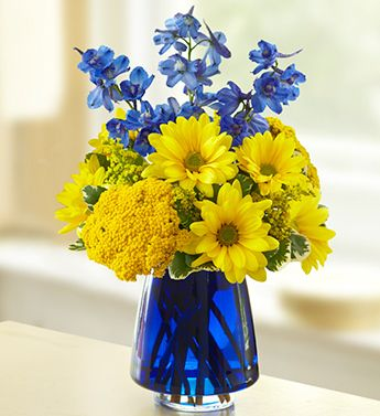 French Countryside™- blue delphinium, yellow poms, yarrow and solidago, accented by variegated pittosporum $39.99
