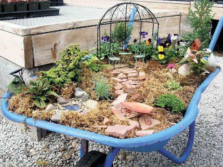 mini jardin de fées dans une brouette avec pensées et allée en morceaux de terre cuite