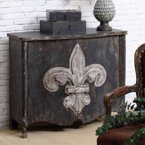 A Wooden Cabinet From Creative Co Op U0027s Turn Of The Century Collection  Showcases An Oversize Weathered Fleur De Lis Against A Rustic Black  Background.