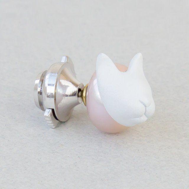 真珠の上にネコを合わせたピンブローチ 猫好きによる猫好きへ向けたピン☆ 猫好きの方へのプレゼントにも人気です こちらの商品金額の15%は、ネコの保護活動を行っている団体へ寄付される寄付金付きのアクセサリーです。 あえて斜めについた猫のパーツは着用時に、着ける人に寄り添ってスリスリしているような姿になります。 猫の顔のむきにより、着用時変わります。 着用する際の猫の顔のむきをご指定下さい。 淡水真珠 染め 約11mm 金具 真鍮 ゴールドコーティング ネコパーツ 樹脂系