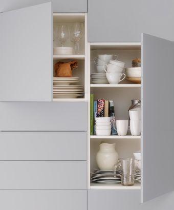 Detalle de unos armarios de cocina de IKEA abiertos. No hay pomos ni tiradores; las puertas se abren presionando.