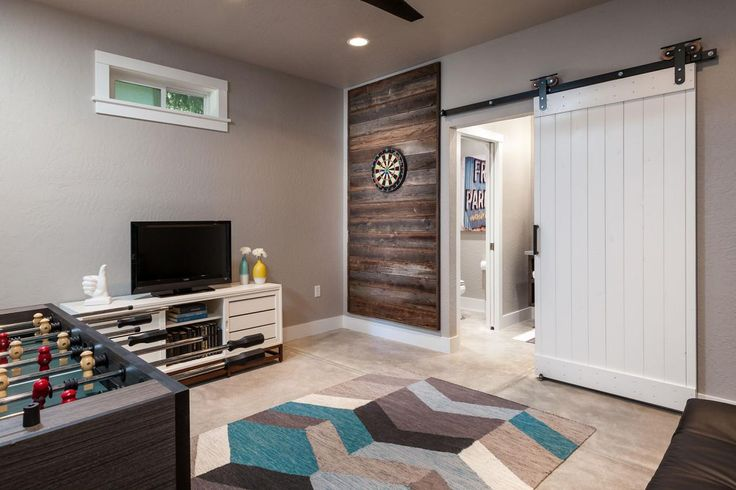 Love the #barn door and the #wood #wall panel in this transitional game room. Check more at www.oklahomahomes.com