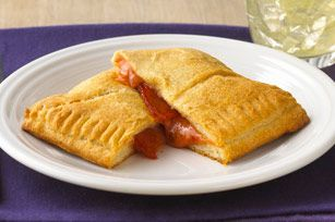 Pizza Calzones - The calzone. A cheesy, saucy, pepperoni-filled slice of heaven—without the pizza drip. #kidsloveit