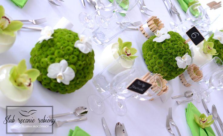 """Biało zielone dekoracje stołu weselnego w całości wykonane przez Agencję Ślubną Sroczyńskich """"Ślub Ręcznie Robiony"""". Świeże, wiosenne, z elementami stylu eko. Zielone świece w drewnianych świecznikach. Dekoracje kwiatowe, to kule z zielonych chryzantem, na których przysiadły białe storczyki. Zielone orchidee pływają w mleku w małych kulistych wazonach. Drewniane tabliczki z numerami stołów i winietki z nazwiskami gości przypięte do kieliszków na drewnianych spinaczach."""